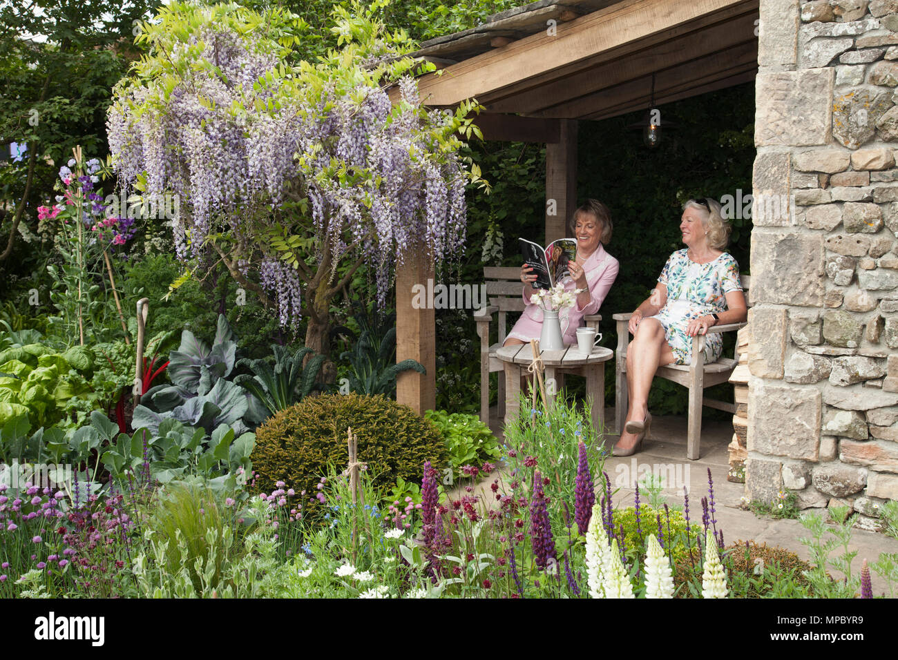 Chelsea, London, UK. 21st May, 2018. Chelsea, London, UK. 21st May 2018. Dame Esther Rantzen and a friend on the Welcome to Yorkshire garden at Chelsea Flower Show 2018, designed by Mark Gregory for Landformconsultants.co.uk Credit: Jenny Lilly/Alamy Live News - Stock Image