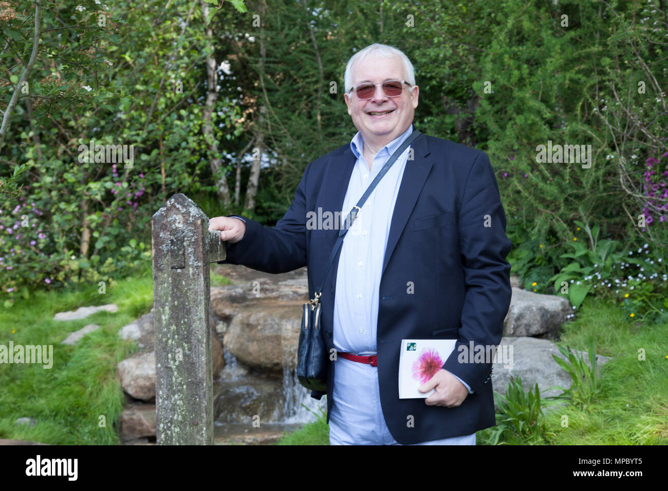 Chelsea, London, UK. 21st May, 2018. Chelsea, London, UK. 21st May 2018. Sir Christopher Biggins on the Welcome to Yorkshire garden at Chelsea Flower Show 2018, designed by Mark Gregory for Landformconsultants.co.uk Credit: Jenny Lilly/Alamy Live News - Stock Image