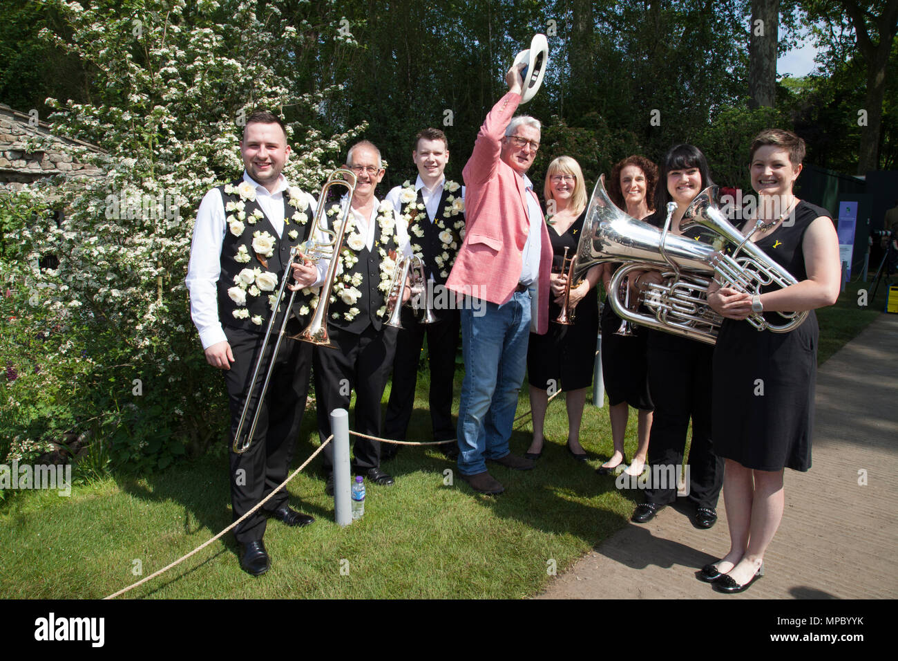 Chelsea, London, UK. 21st May, 2018. Chelsea, London, UK. 21st May 2018. Jeremy Paxman with the City of Bradford Brass Band on the Welcome to Yorkshire garden at Chelsea Flower Show 2018, designed by Mark Gregory for Landformconsultants.co.uk Credit: Jenny Lilly/Alamy Live News - Stock Image