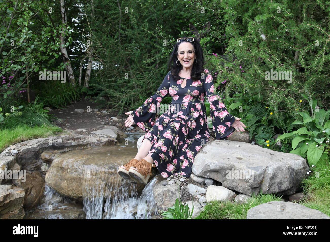 Chelsea, London, UK. 21st May, 2018. Chelsea, London, UK. 21st May 2018. Lesley Joseph taking at break in the Welcome to Yorkshire garden at Chelsea Flower Show 2018, designed by Mark Gregory for Landformconsultants.co.uk Credit: Jenny Lilly/Alamy Live News - Stock Image
