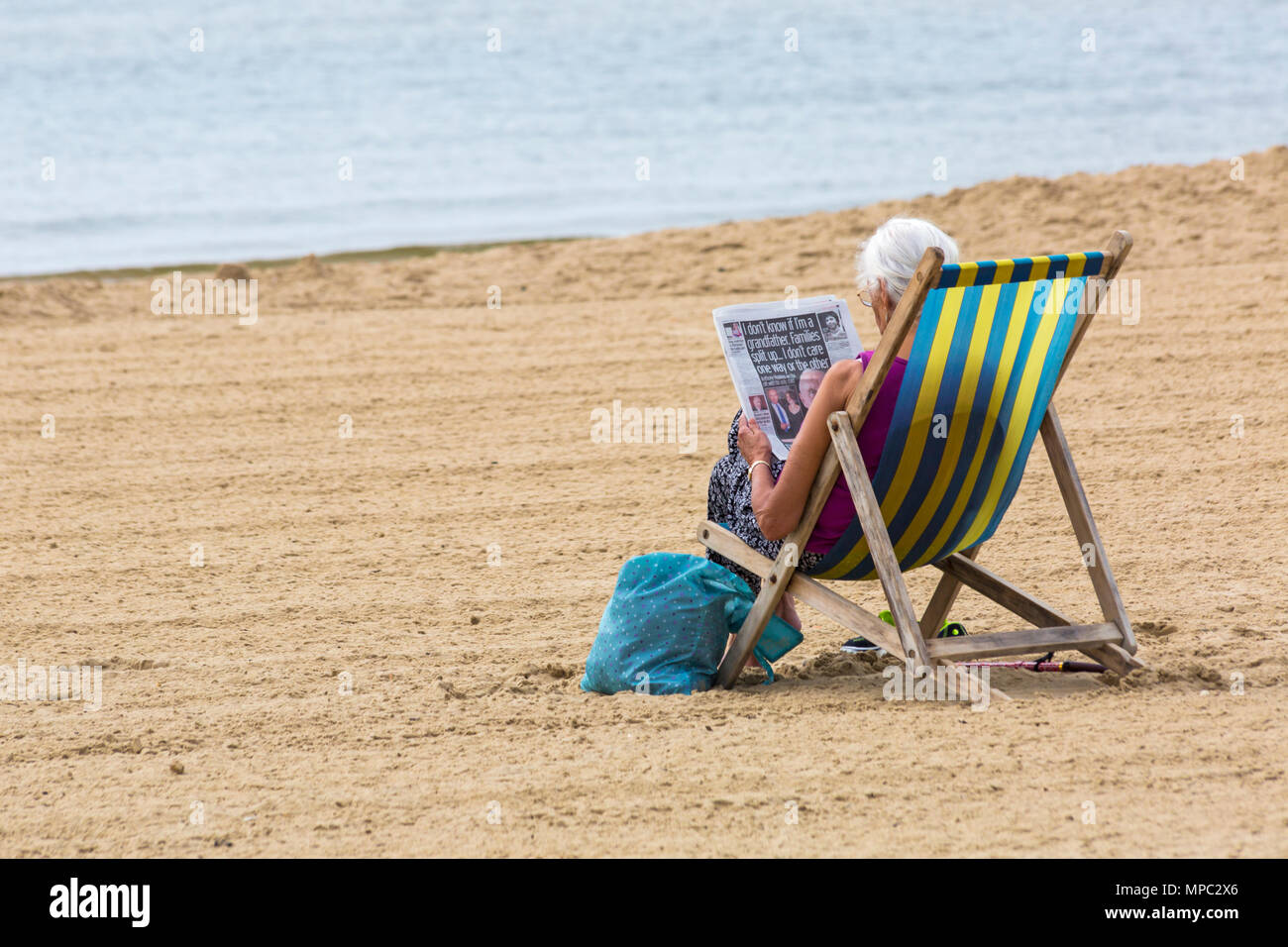 Bournemouth, Dorset, UK. 22nd May 2018. UK weather: after a cloudy overcast start to the day the sun returns and visitors head to the beach to enjoy the sunshine. Woman reads newspaper in deckchair. Credit: Carolyn Jenkins/Alamy Live News - Stock Image