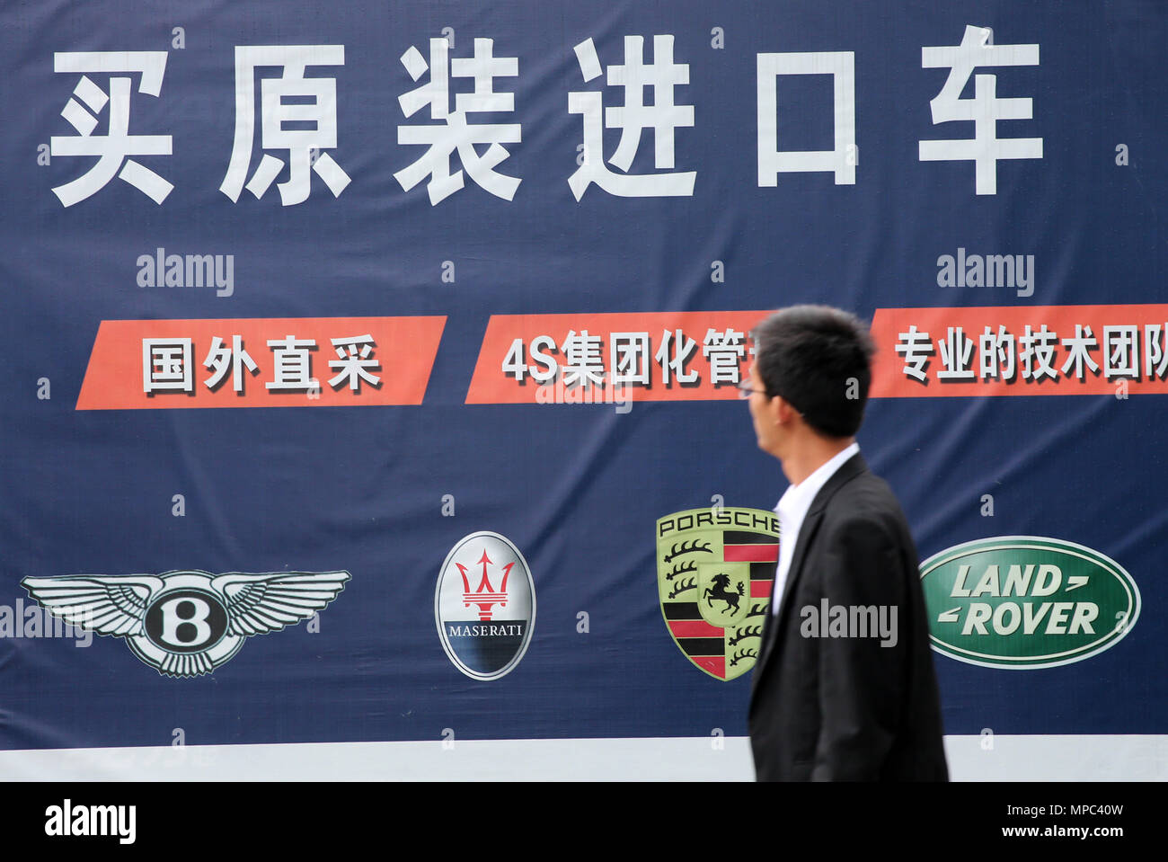 (180522) -- NANTONG, May 22, 2018 (Xinhua) -- A man walks past an auto billboard in Nantong, east China's Jiangsu Province, May 22, 2018. China will cut import tariffs on vehicles and auto parts starting July 1, the Ministry of Finance (MOF) announced Tuesday. For car imports, the 25-percent tariff levied on 135 items and the 20-percent duty on four items will both be slashed to 15 percent, down 40 percent and 25 percent respectively. Import tariffs for 79 items of auto parts will be reduced to 6 percent from the current levels of 8 percent, 10 percent, 15 percent, 20 percent, and 25 percent, - Stock Image