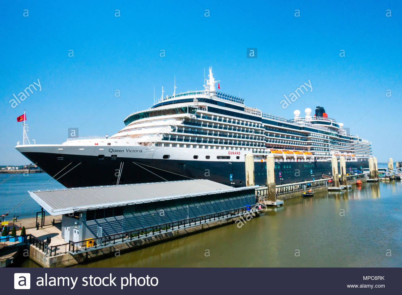 The Cunard Cruise Liner Queen Victoria berthed at the Pier Head in Liverpool, the large passenger ship berthed on a sunny day, on it's arrival in Liverpool, Merseyside, England on a very sunny day. Credit: Christopher Canty Photography/Alamy Live News - Stock Image