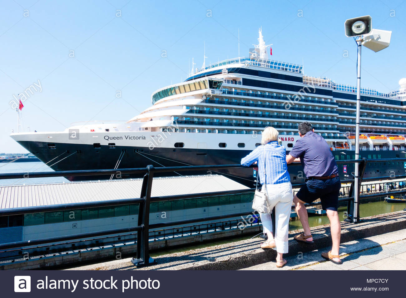 The Cunard Cruise Liner Queen Victoria berthed at the Pier Head in Liverpool, People on their lunch break admire the large passenger ship on it's arrival in Liverpool, Merseyside, England on a very sunny day. Credit: Christopher Canty Photography/Alamy Live News Stock Photo