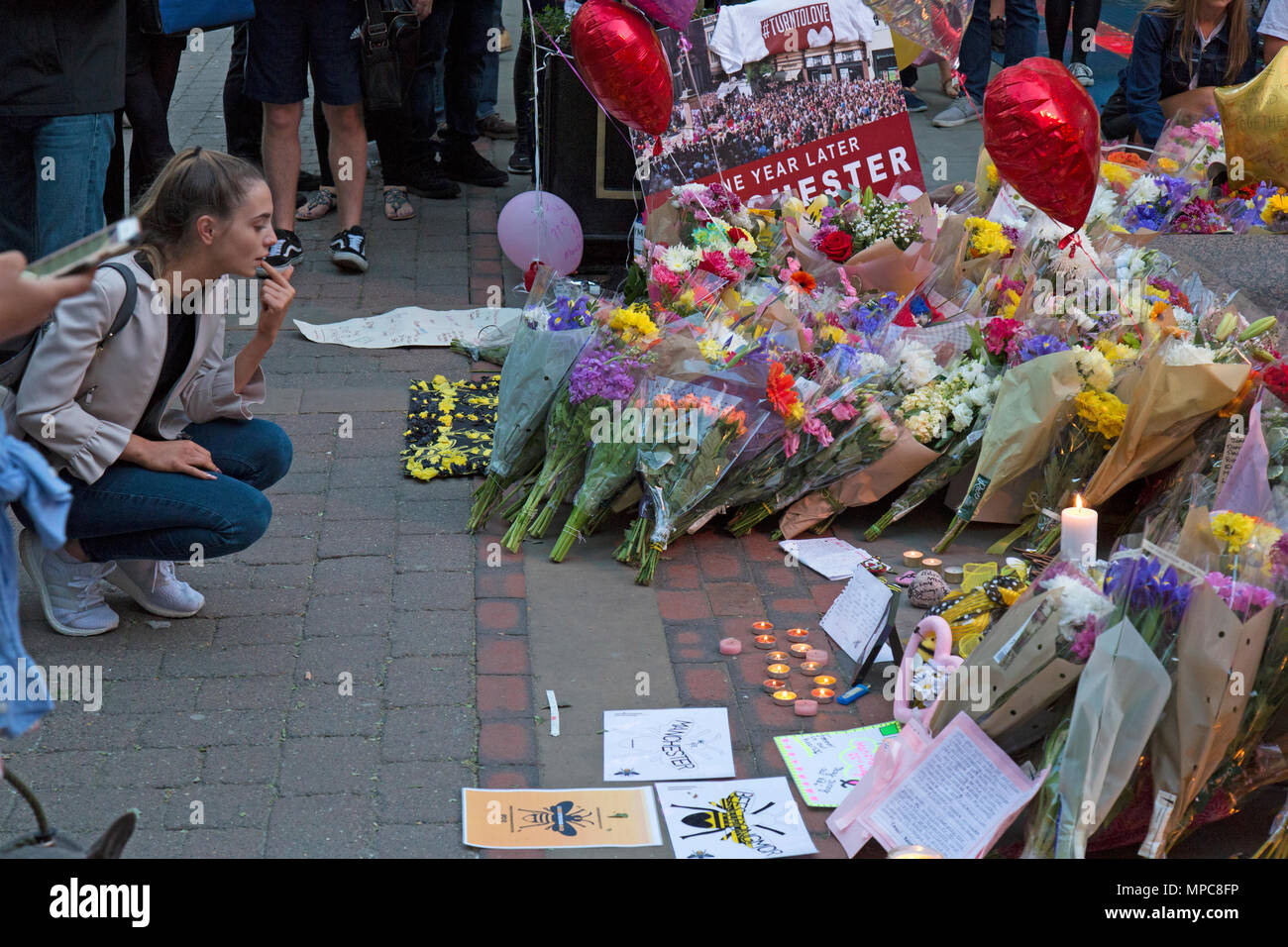 Manchester, UK. 22nd May, 2018. Young female looking at the floral tributes left in St. Ann's Square in the center of Manchester, to remember the 22 victims of the bombing of the Manchester Arena, following the concert given by the American singer Ariana Grande. Credit: Rob Carter/Alamy Live News - Stock Image