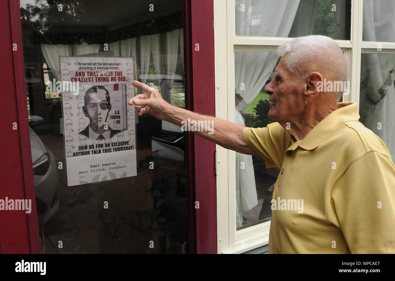 Florida, USA. 22nd May, 2018. Carl Laurin, the author of the book, 'D.B. Cooper & Me: A Criminal, a Spy, My Best Friend', which was released on May 17, 2018, points to an advertisement for the book at his home on May 22, 2018 in DeLand, Florida. The book chronicles the confessions of Laurin's longtime friend, Walter R. Reca, who, around 2008, related to Laurin that he committed the infamous 1971 hijacking of a Northwest Orient flight from Portland to Seattle. Credit: Paul Hennessy/Alamy Live News - Stock Image