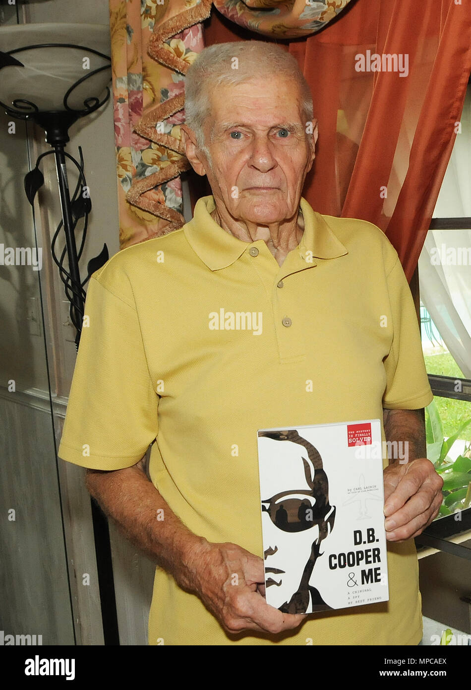 Florida, USA. 22nd May, 2018. Carl Laurin poses on May 22, 2018 at his home in DeLand, Florida with a copy of his book, 'D.B. Cooper & Me: A Criminal, a Spy, My Best Friend', which was released on May 17, 2018. The book chronicles the confessions of Laurin's longtime friend, Walter R. Reca, who, around 2008, related to Laurin that he committed the infamous 1971 hijacking of a Northwest Orient flight from Portland to Seattle. Credit: Paul Hennessy/Alamy Live News - Stock Image
