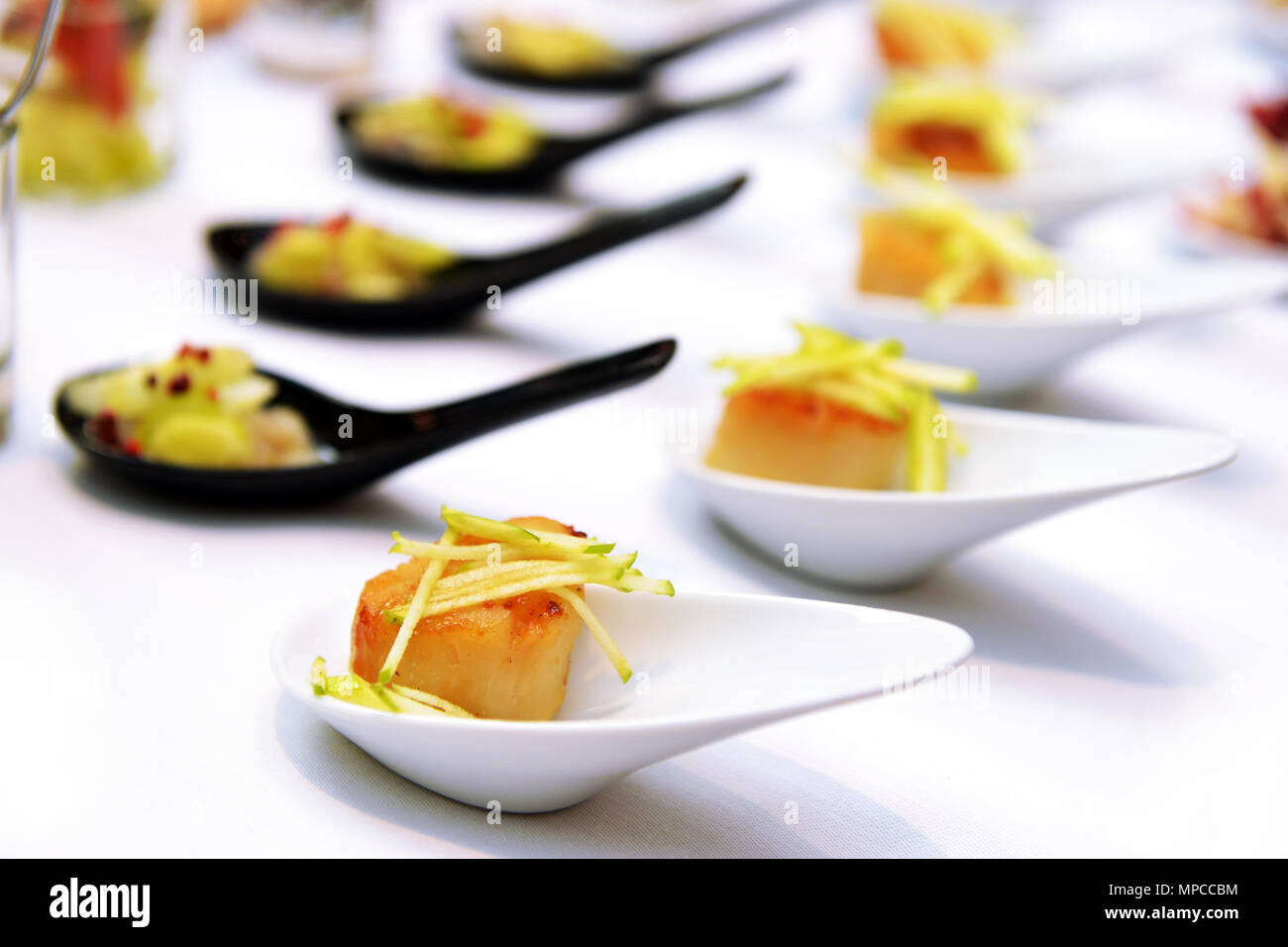 scallops in the spoon on the buffet table - Stock Image