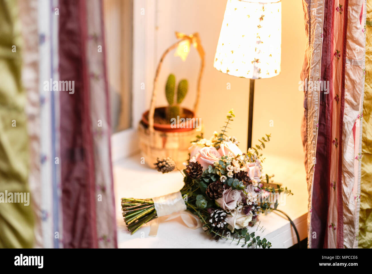 Wedding bride bouquet of fresh floral. White ranunculus flowers on table. warm evening atmosphere - Stock Image