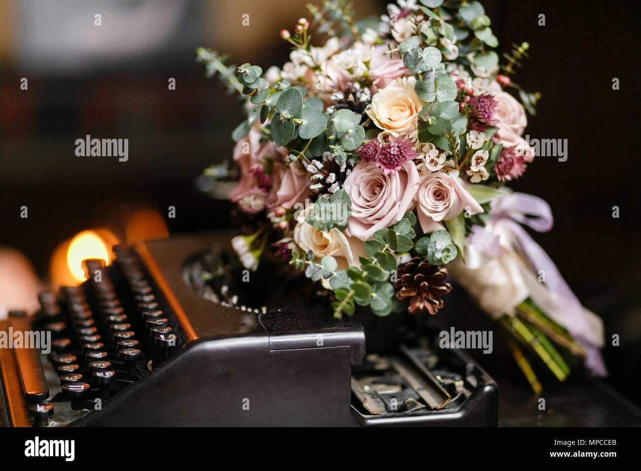 Wedding bride bouquet of fresh floral. White ranunculus flowers on typewriter,. - Stock Image