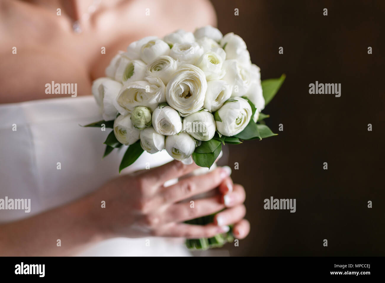 Wedding bride bouquet of fresh floral. White ranunculus flowers in womans hand. - Stock Image