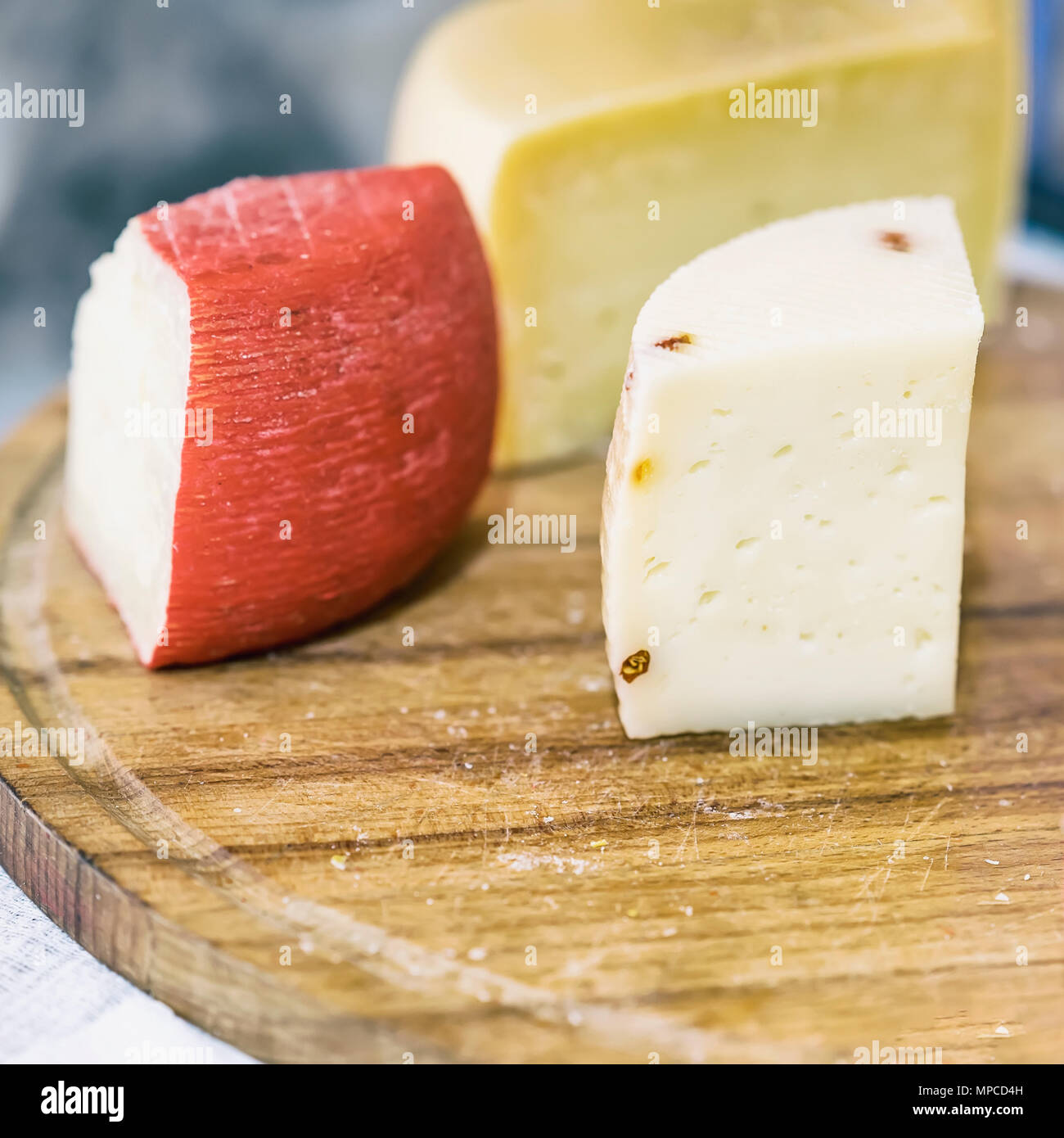 Pieces heads of soft cheeses with different additives on wooden market board. Gastronomic dairy produce, real scene in the food market, square - Stock Image