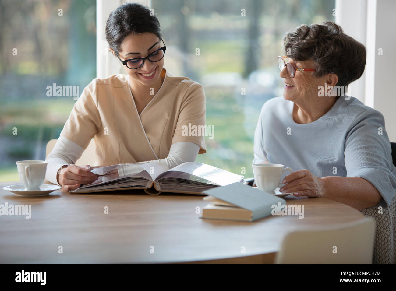 Happy senior woman spending time together with a tender caregiver sitting by a table and looking at family photo album against blurred background of w - Stock Image
