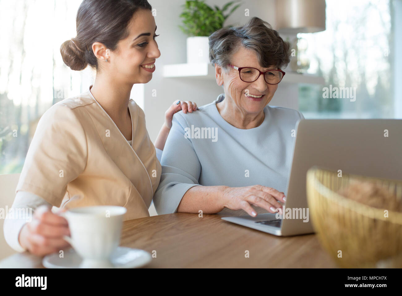 Tender caretaker closing the generation gap and teaching a smiling senior woman the use of Internet on a laptop while sitting by a table in a bright r - Stock Image