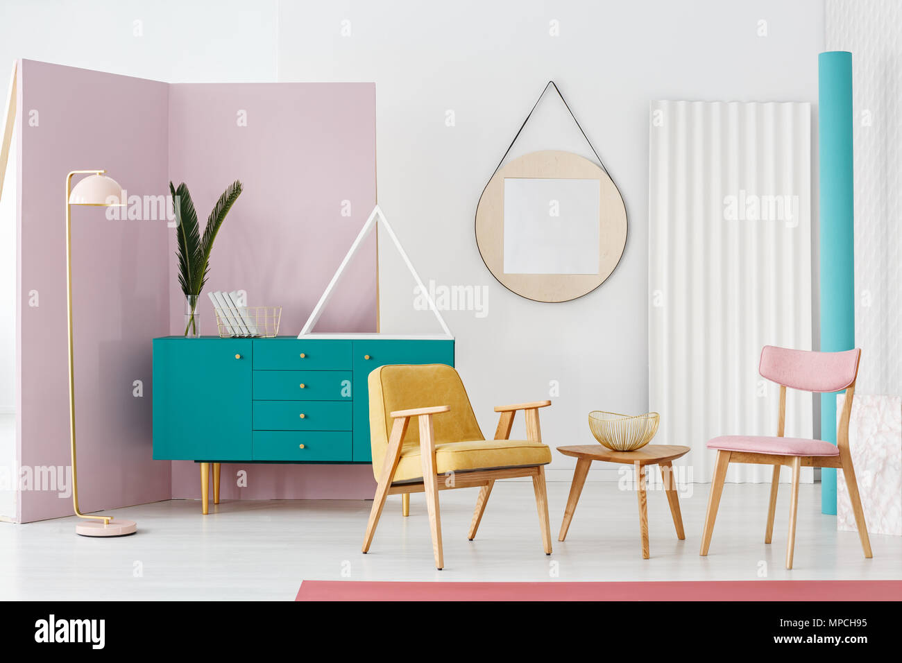 Wooden table between yellow armchair and pink chair in colorful ...