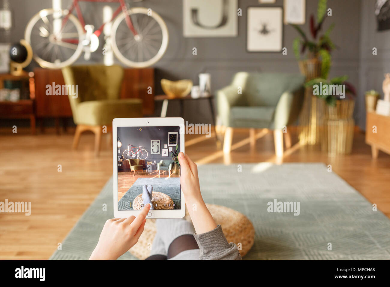 A woman relaxing holding a tablet and using a touch screen while comfortably lying down on a green carpet in a vintage flat interior with blurred back Stock Photo