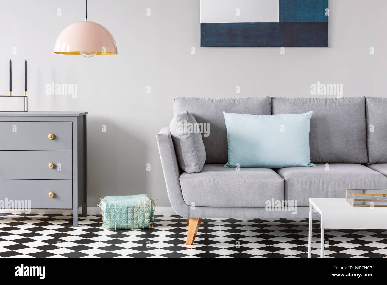 Pink Lamp Above Grey Cabinet Next To Sofa On Checkered Floor In Pastel  Living Room Interior. Real Photo