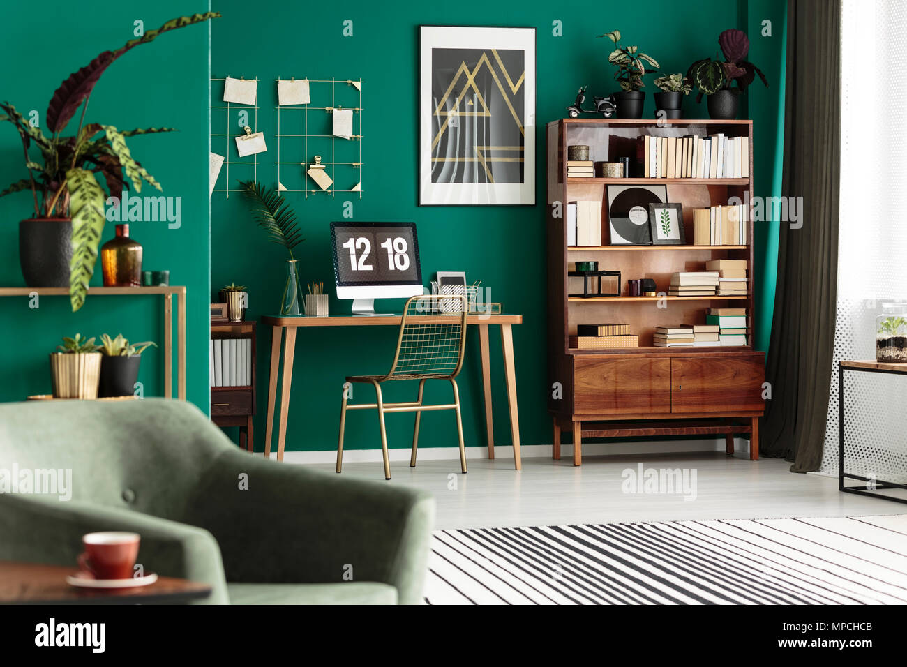 Gold chair at desk with desktop computer in green, cozy apartment interior with poster - Stock Image