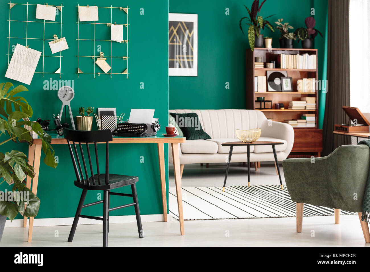 Black chair at wooden desk in green open space interior with armchair and couch - Stock Image