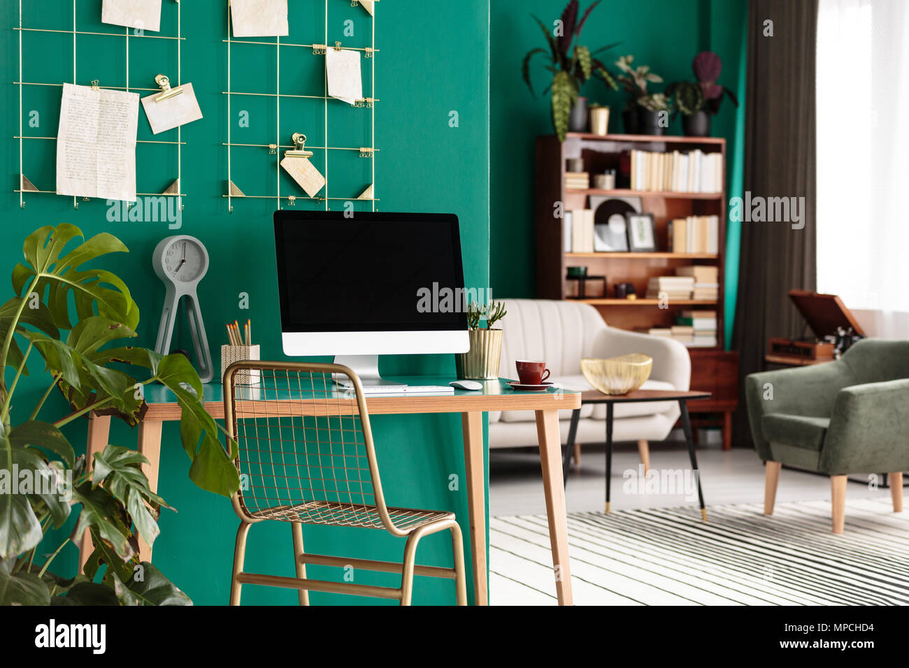 Gold chair at wooden desk with desktop computer in home office interior with plant against green wall - Stock Image