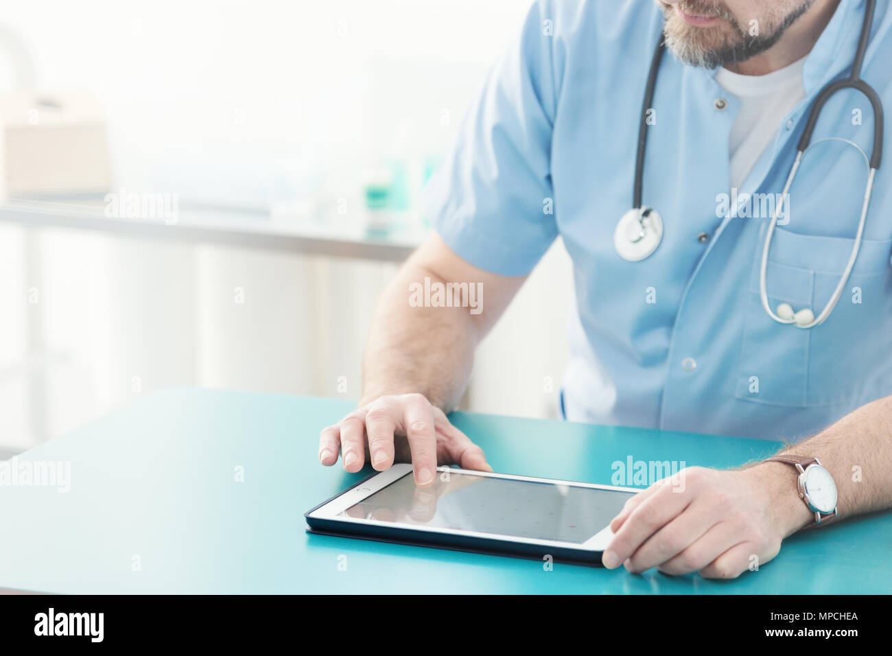 Close-up of doctor with stethoscope using tablet during work - Stock Image