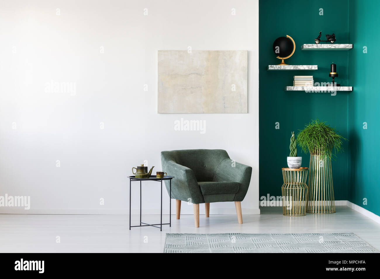 Simple Living Room Interior With Green Armchair Plants Teapot Set On The Table And Marble Shelves On The Wall Stock Photo Alamy