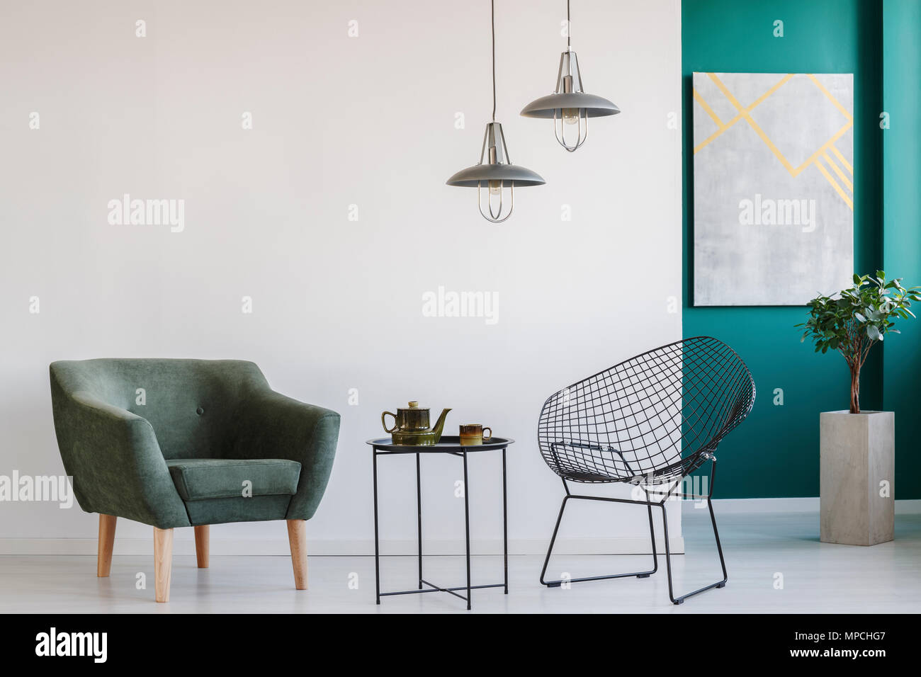 Modern living room interior with two armchairs, lamps, teapot set on ...