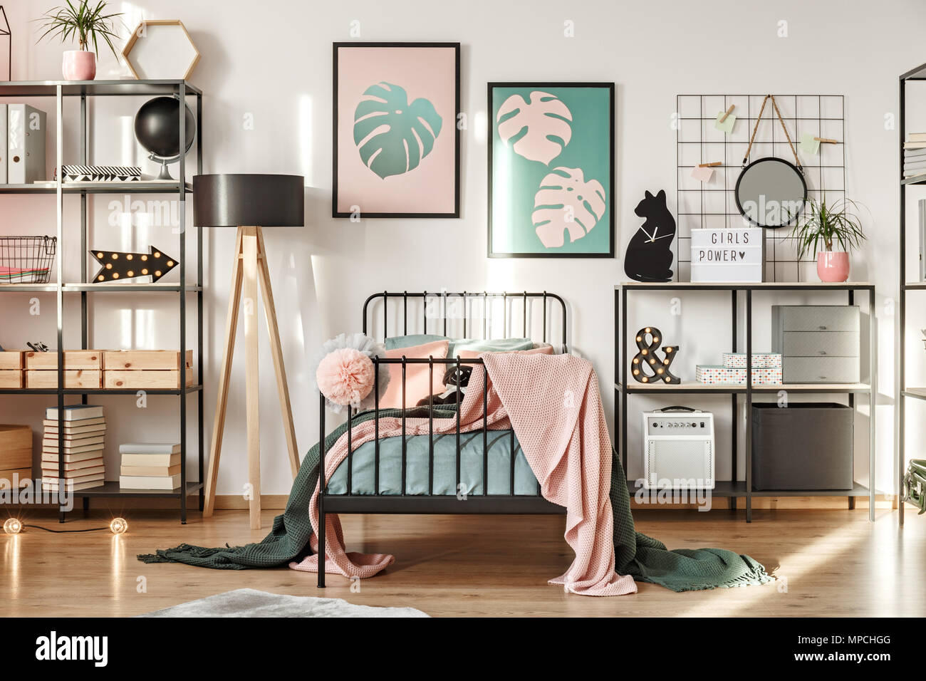 Metal shelves with decorations, botanical posters and comfy bed in a girl bedroom interior - Stock Image