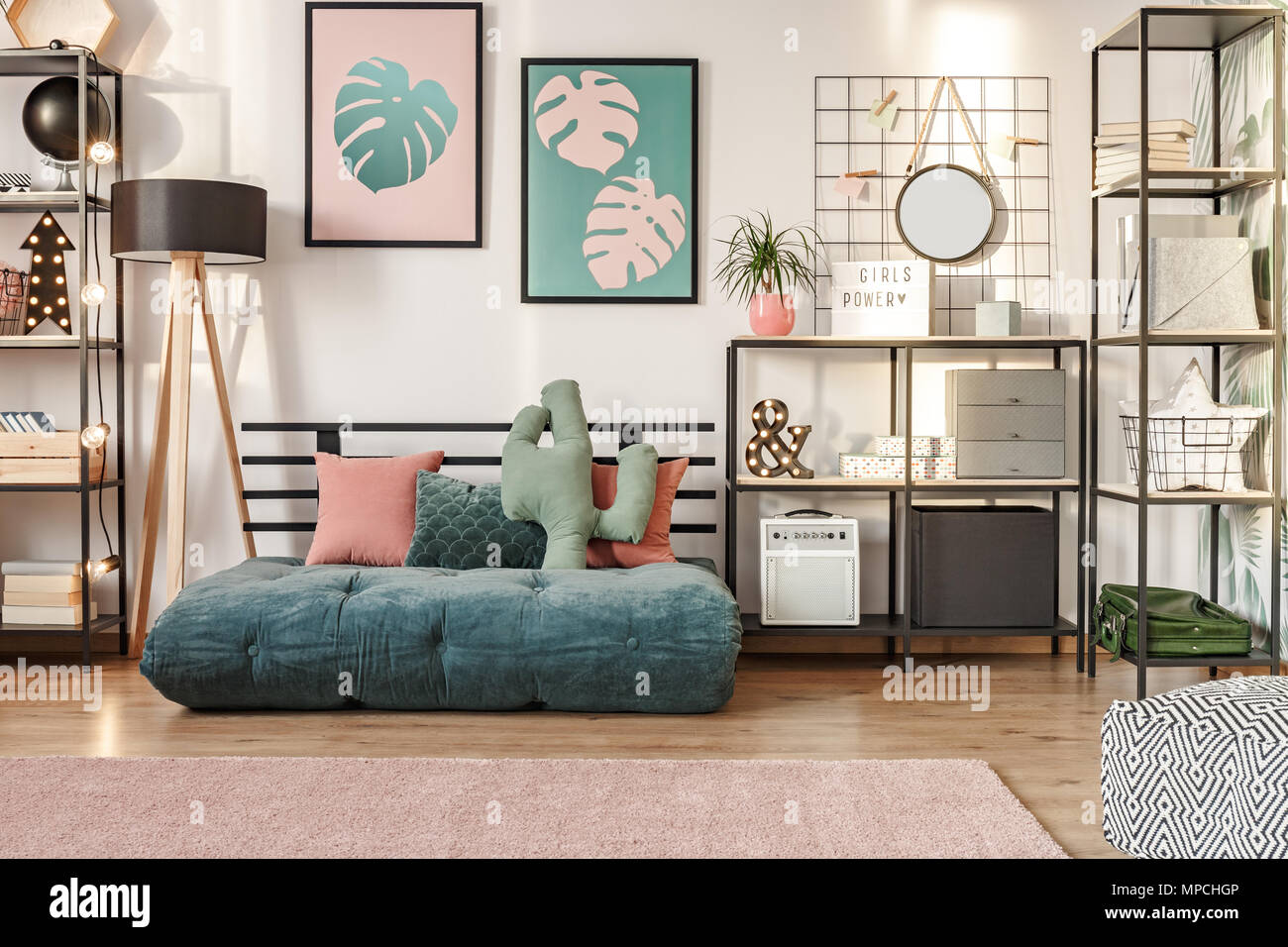 Emerald mattress with a cactus shape pillow, metal shelves and botanical posters in a modern living room interior Stock Photo