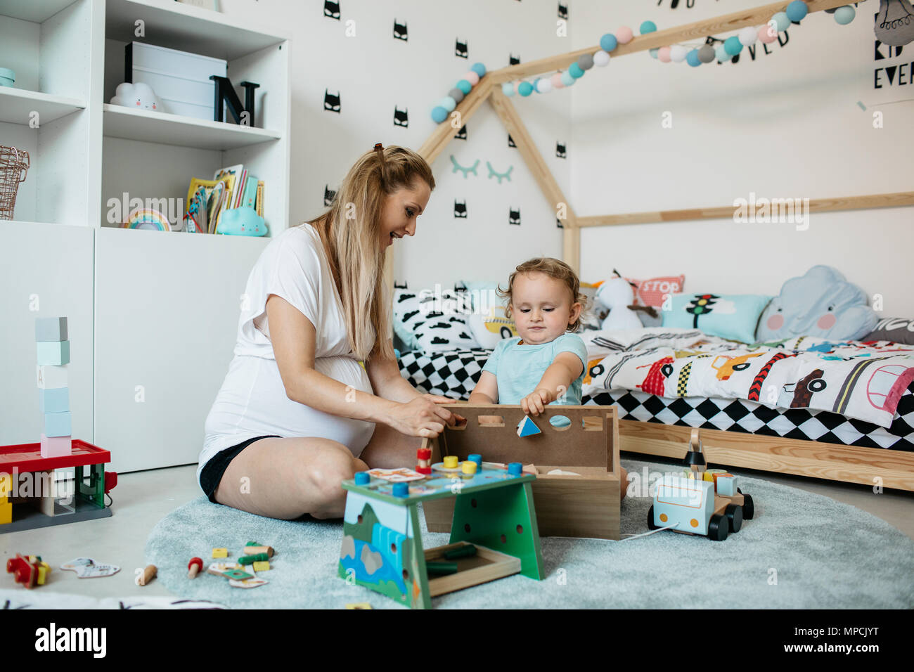 A mother teaches her child geometric shapes and colors. A little boy trying to sort geometric shapes and his mom encouraging him. - Stock Image