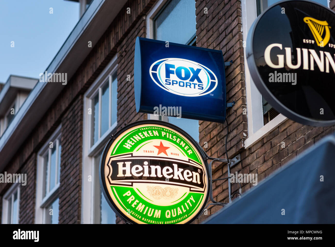 Fox Sports, Heineken and Guinness logos outside a bar in Alkmaar, Netherlands. Fox Sports live broadcasts professional soccer in The Netherlands. - Stock Image