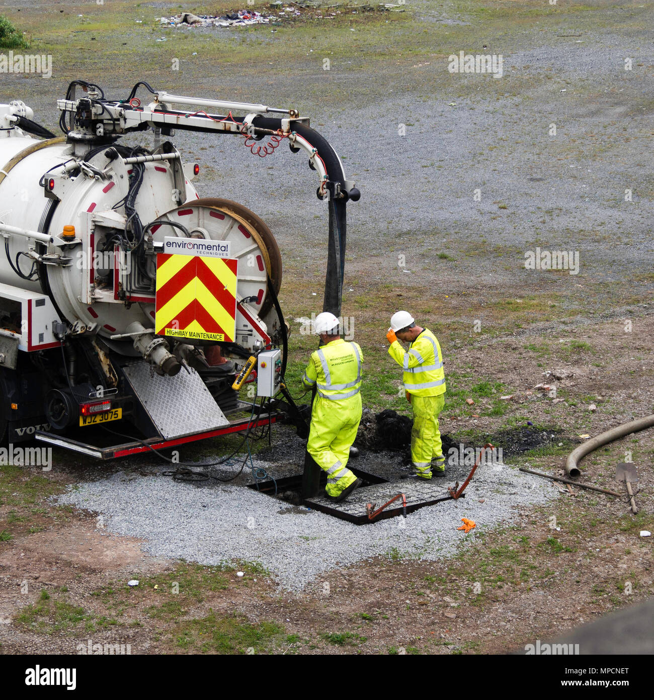 Workmen in high vis jackets operating equipment to clear drains - Stock Image