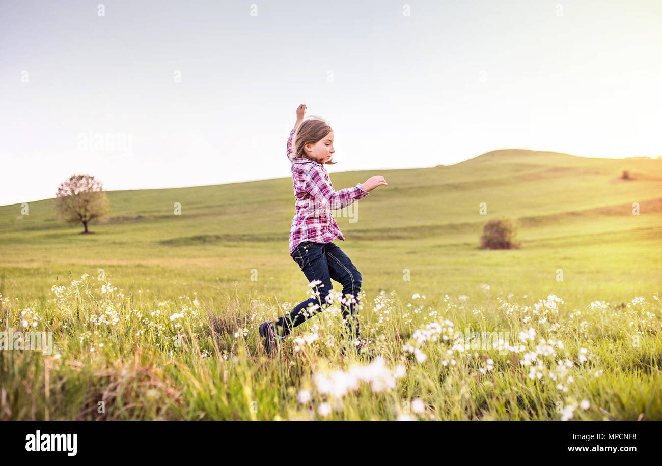 A small girl having fun outside in nature. - Stock Image