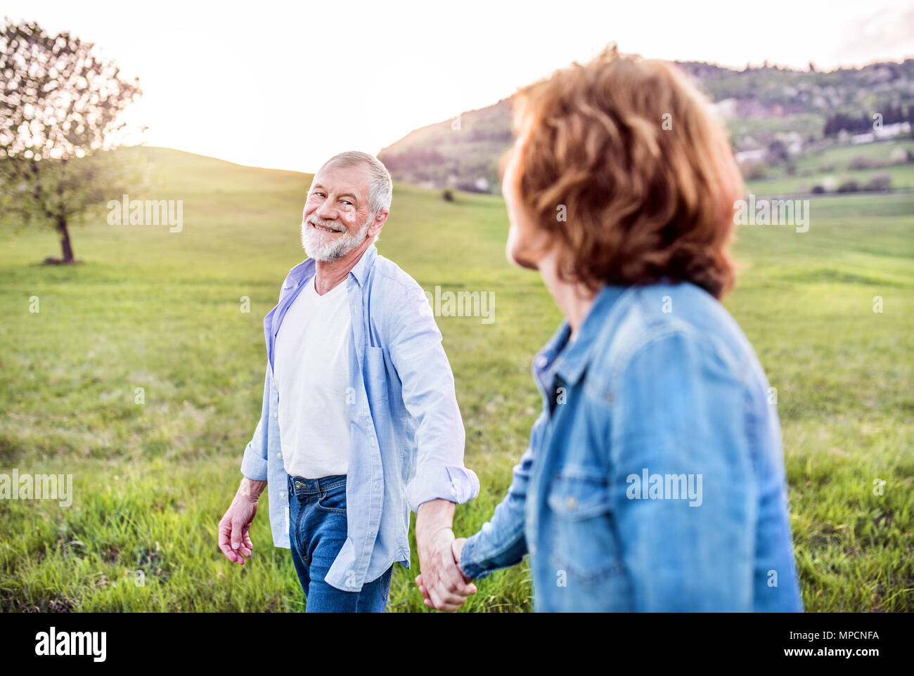 Senior couple walking outside in spring nature, holding hands. - Stock Image