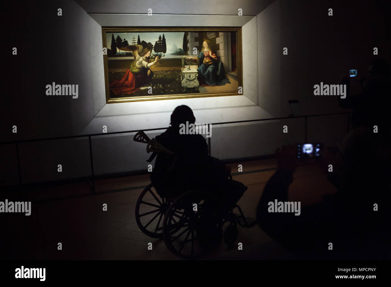 Disabled person in the wheelchair in front of the painting Annunciation (1472–1475) by Italian Renaissance painter Leonardo da Vinci displayed in the Uffizi Gallery (Galleria degli Uffizi) in Florence, Tuscany, Italy. - Stock Image