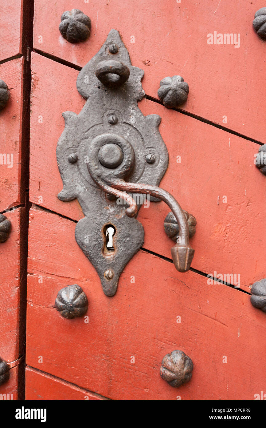 Ancient Rusty lock and door knob at Kronborg  Slot: An old rusty lock and handle on a wooden orange red door reinforced with large iron rivets. - Stock Image