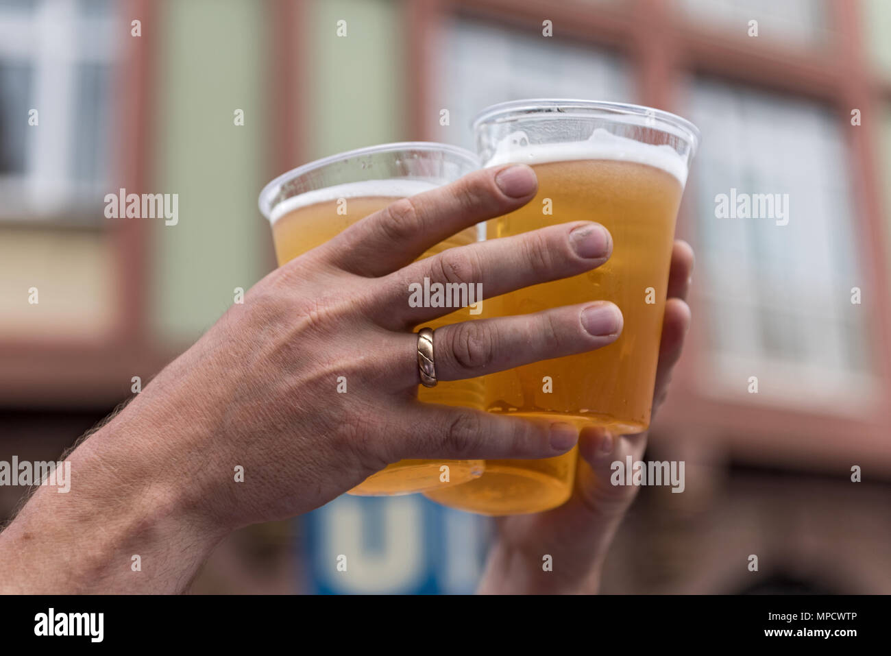 two hands and three full plastic cups with beer - Stock Image