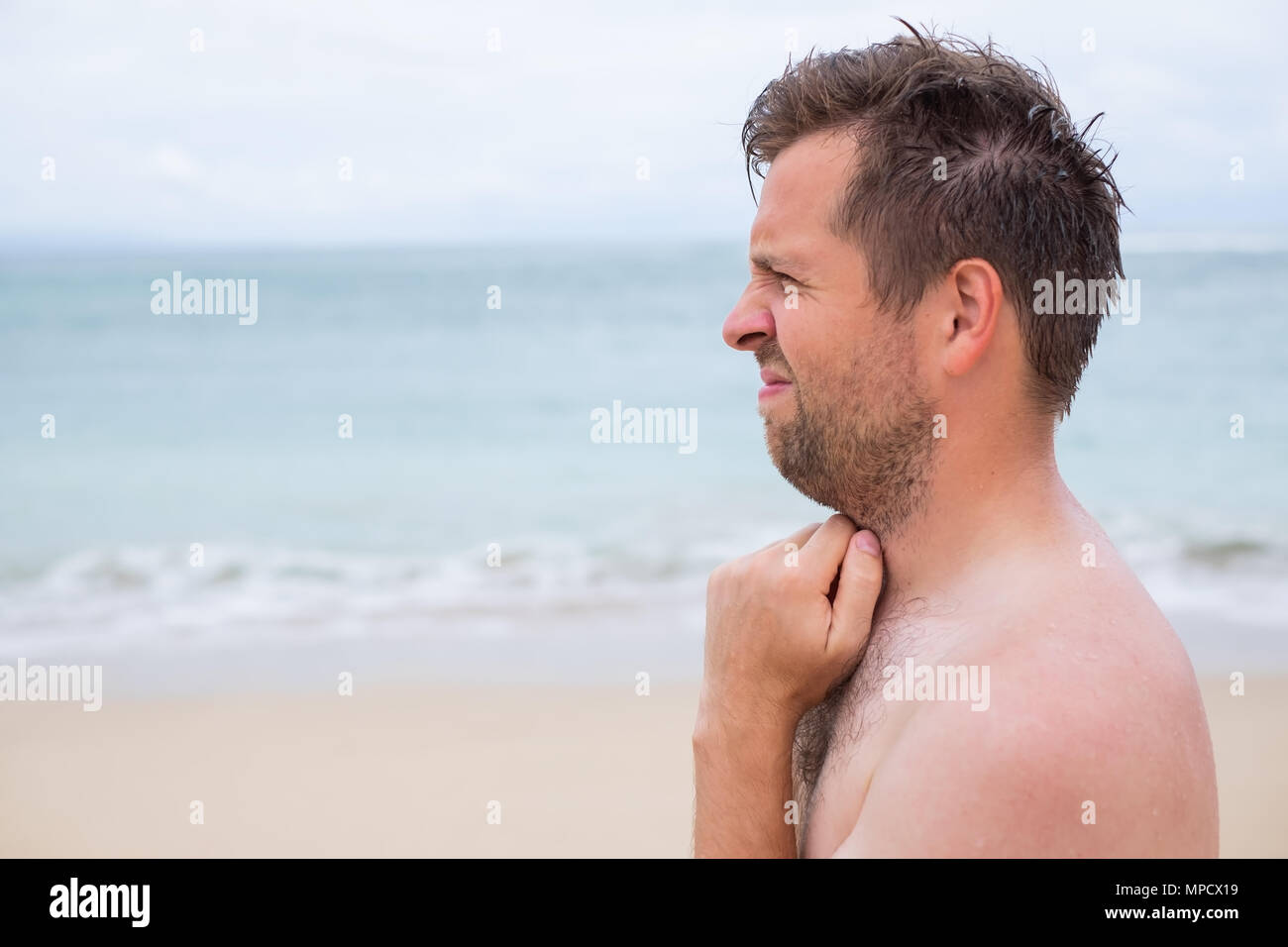 Worried caucasian man sucking his thumb standing on the tropical beach - Stock Image