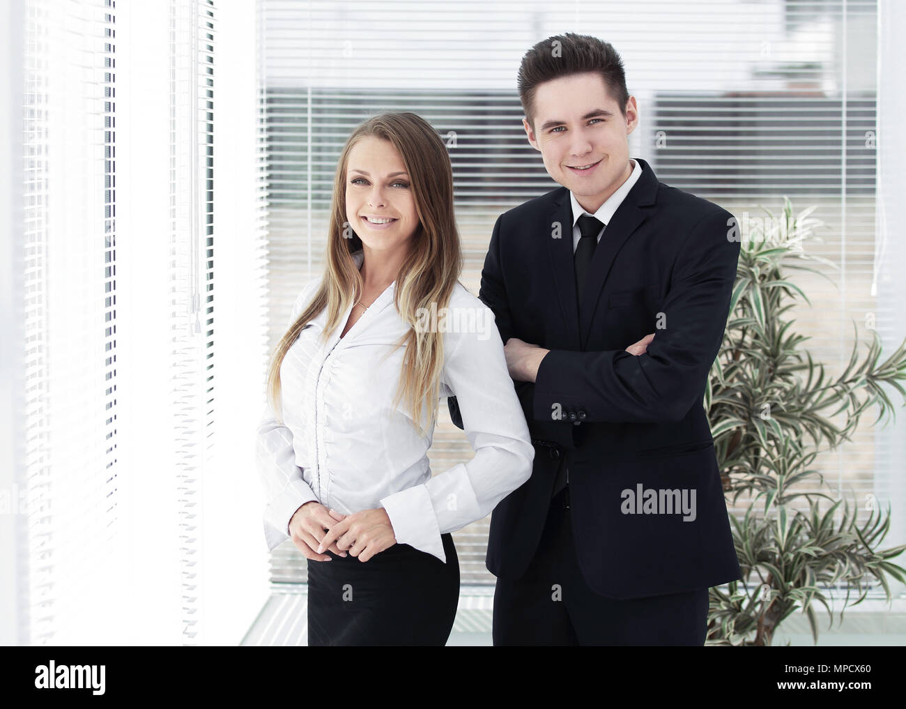 business couple standing in a modern office - Stock Image