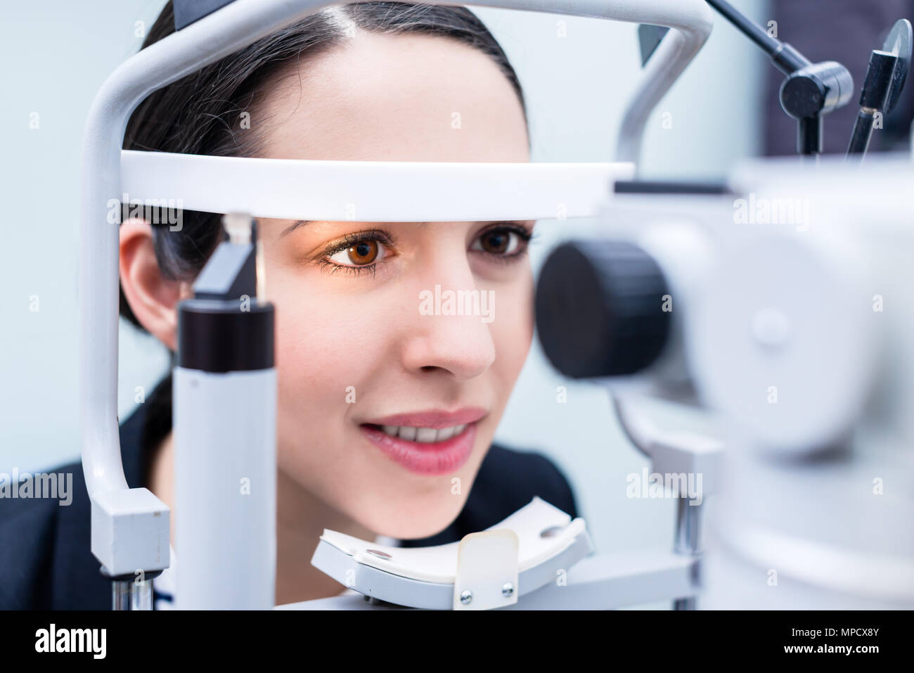 Woman having eyes measured with test device - Stock Image