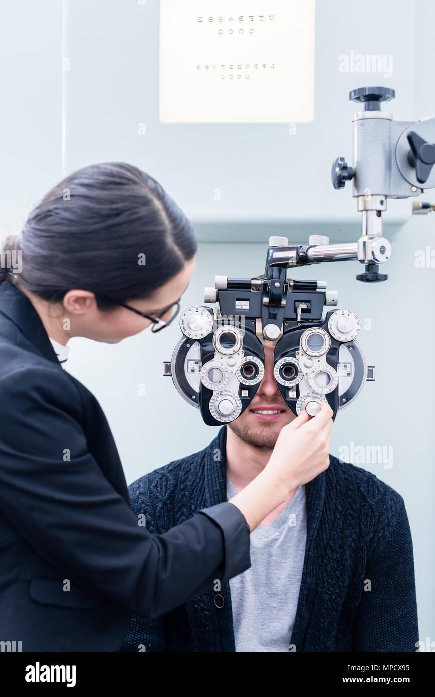 Optician and man at eye examination with phoropter - Stock Image