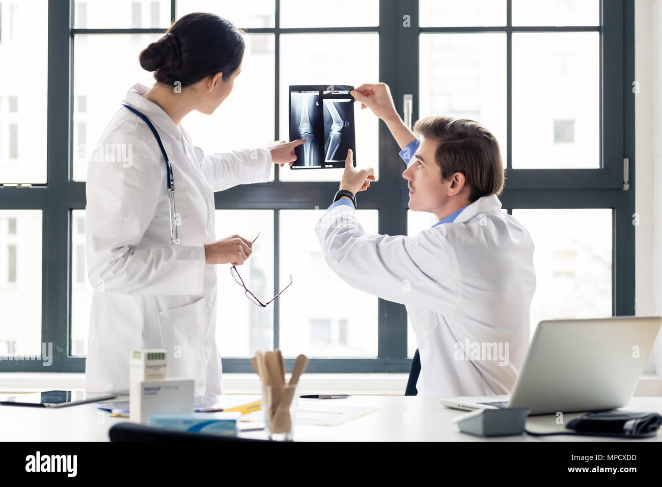 Experienced orthopedist helping his colleague - Stock Image