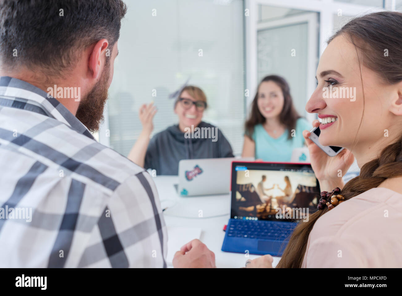 Creative female freelancer smiling to co-worker while making a call - Stock Image