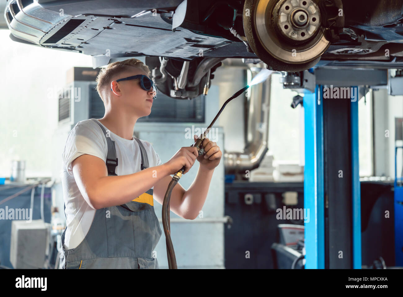 Portrait of a handsome auto mechanic looking at camera with confidence - Stock Image