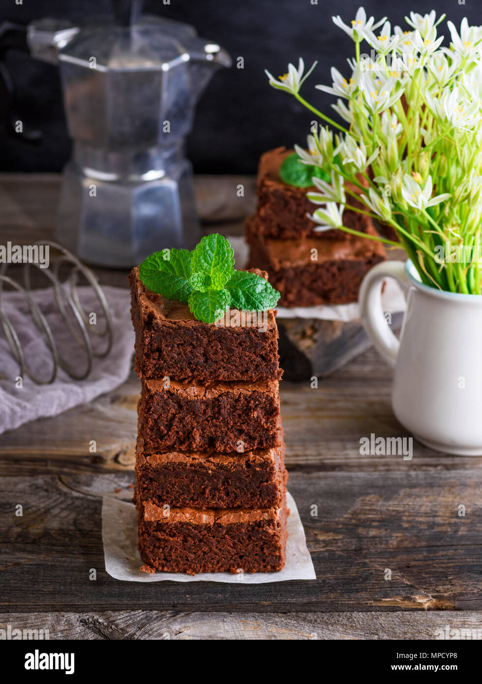 a pile of square pieces of baked brownie on a gray wooden table,  close up - Stock Image