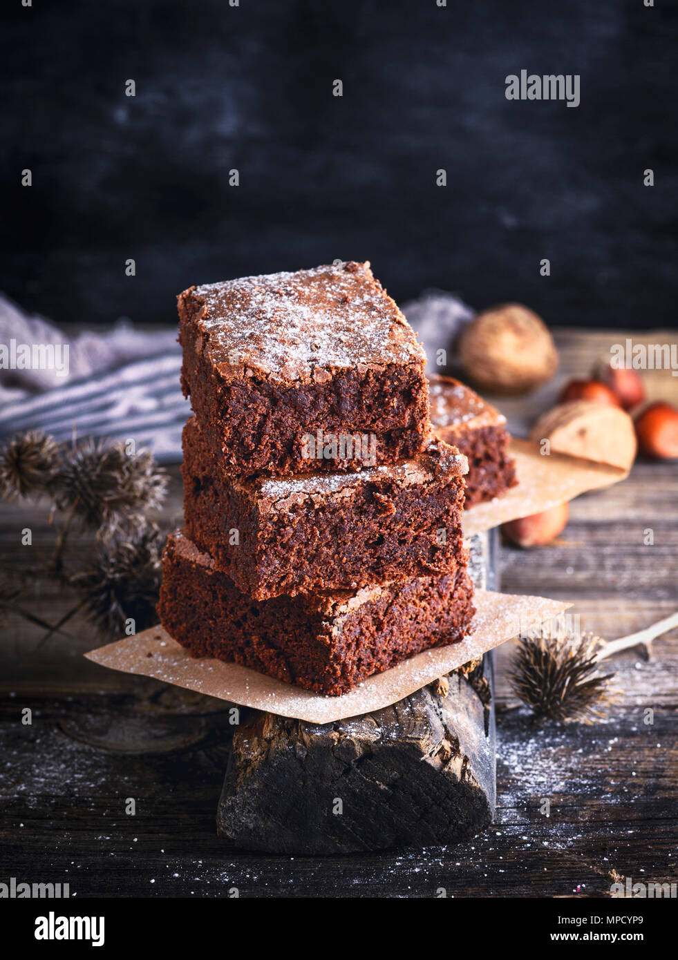 square pieces of chocolate baked brownie pie on a wooden board, close up - Stock Image