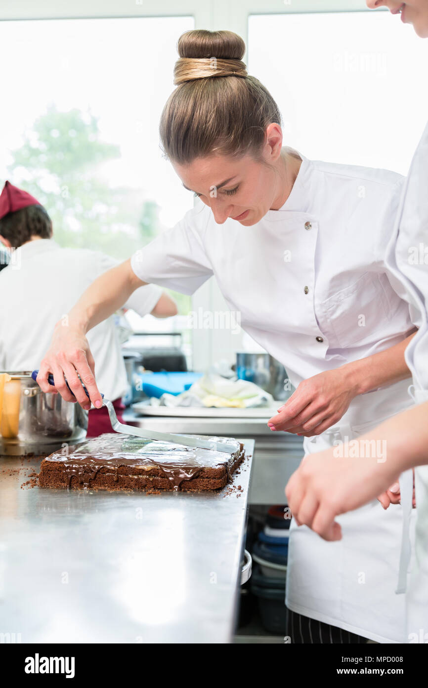 Confectioner putting chocolate as frosting on cake Stock Photo