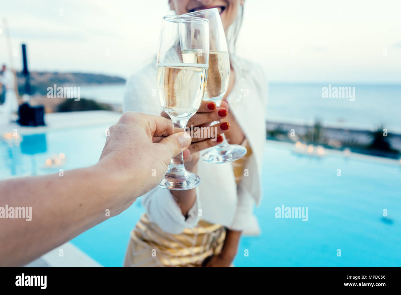 Woman and man clinking glasses at pool party - Stock Image