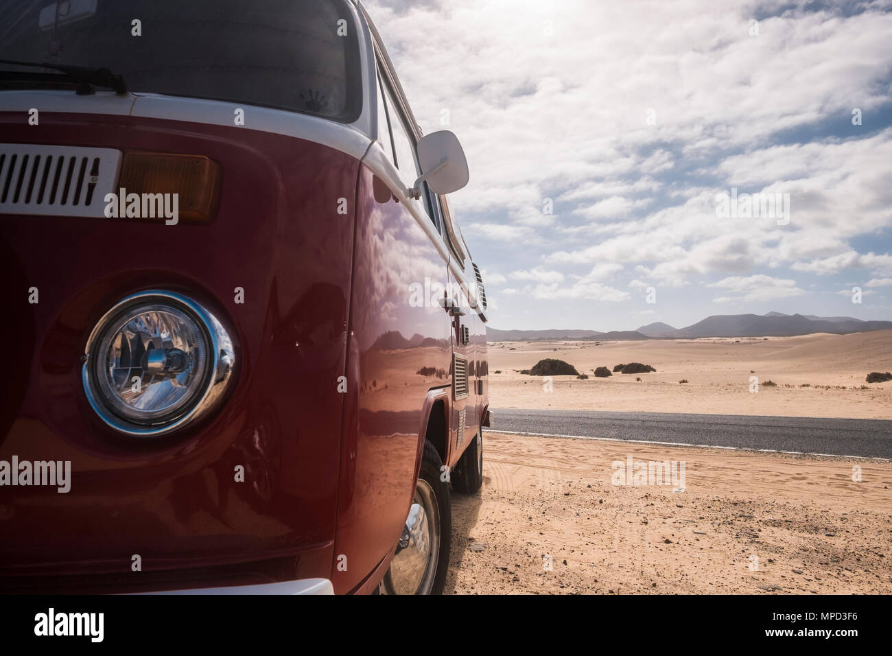 vintage style bus old parked near a road the cross the desert of corralejo in fuerteventura. travel concept for alternative vacation Stock Photo