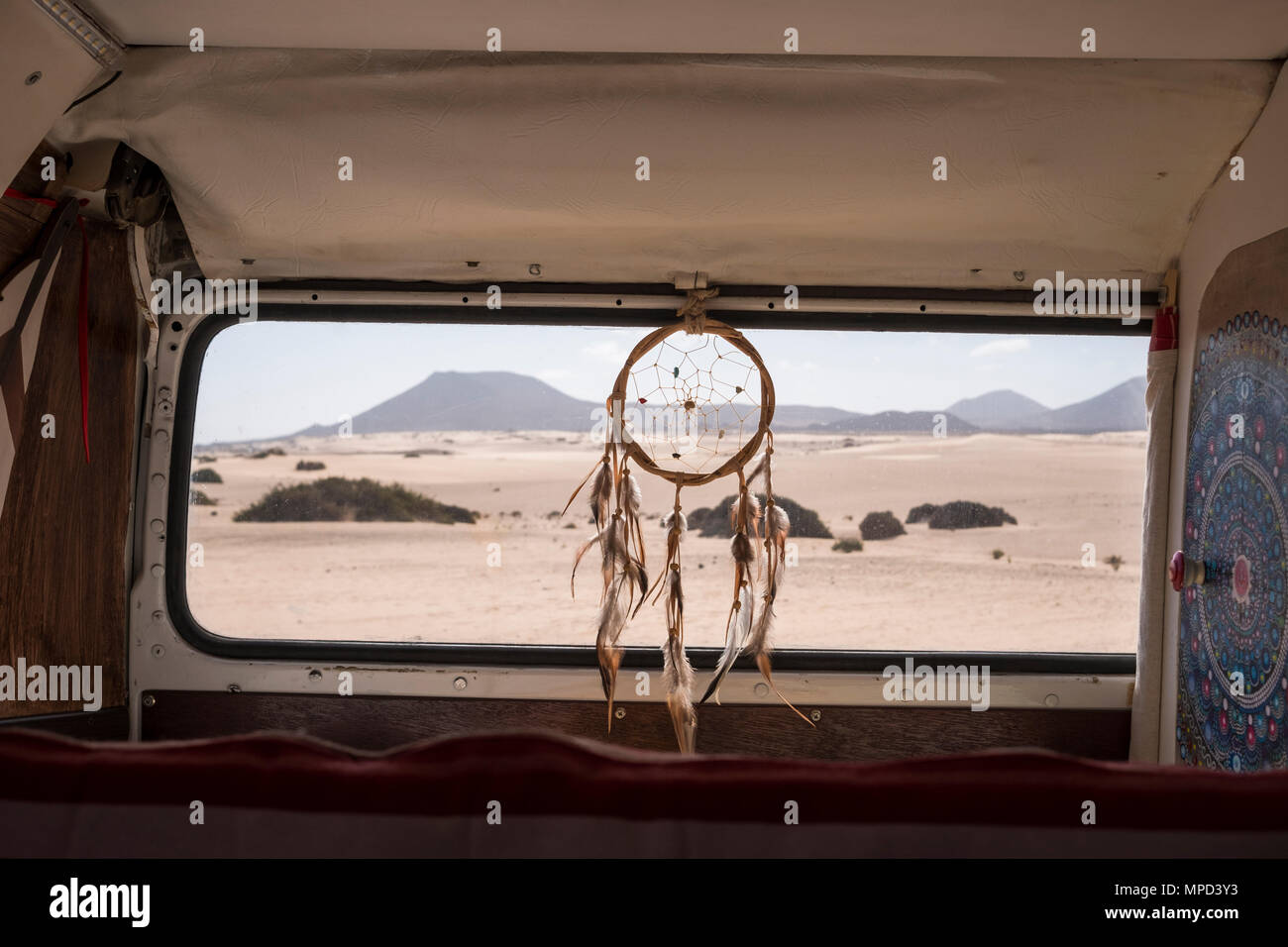 vanlife concept for different alternative life and wy of travel. Dreamcatcher on the window with desert and mountains outdoor. mandale at the left, qu - Stock Image